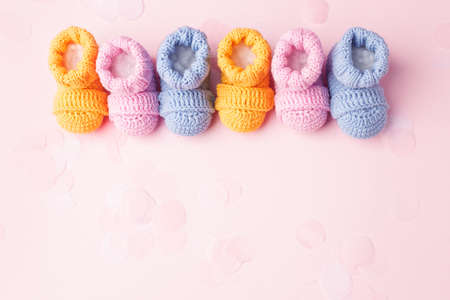 Pregnancy motherhood perenthood concept, Three pairs of baby booties on pink background