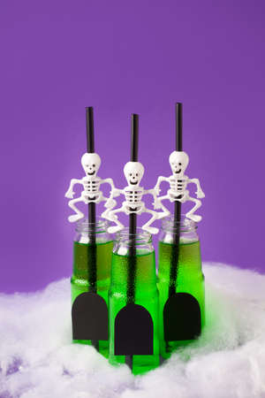 Set of Green witch drink in glass bottles with spooky skeleton cocktail straws and tombs copy space, Halloween funny food idea, bright congratulation, invitation card for seasonal holiday party, menu