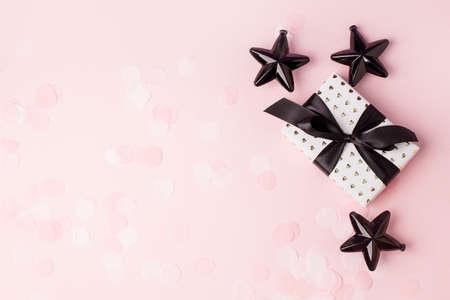 Beautiful minimal Christmas black decor and paper craft gift box with satin black ribbon on dark black background. Flat lay design, flyer, invitation, postcard. Copy Space. Horizontal.