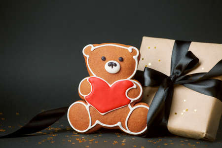 Stylish papercraft gift box and cookies bear with red heart, Concept of seasonal february Saint Valentine's day, mother day, love romance dark black background