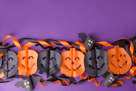 Halloween decorations on bright purple background. Halloween concept. Flat lay, top view, copy space. Party garland and handmade papercraft toy bats from toilet roll, easy diy creative idea for kids