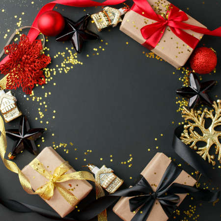 Luxury Christmas frame made of gift boxes, festive decorations, satin ribbon on black table. Christmas, happy new year background.