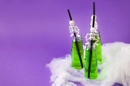 Set of Toxic Green cucumber cocktail for Halloween in glass bottles with decorative straw skeleton and white spider web on trdaitional bright purple background, party flyer, coupon concept Banco de Imagens