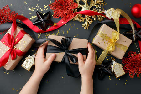 Craft gift boxes on a dark background, decorated with bow and glitter, kids hands, creating a event atmosphere. xmas, happy new year, anniversary presents, sale coupon concept