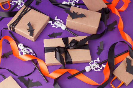 Halloween gift boxes with ribbon and paper decoration on traditional purple background.
