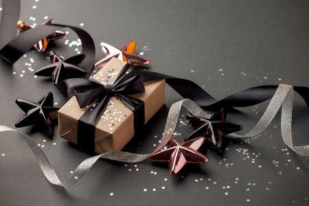 Beautiful christmas black silver decorative toys star snowflakes on dark black background. Flat lay design. Copy Space. Banco de Imagens