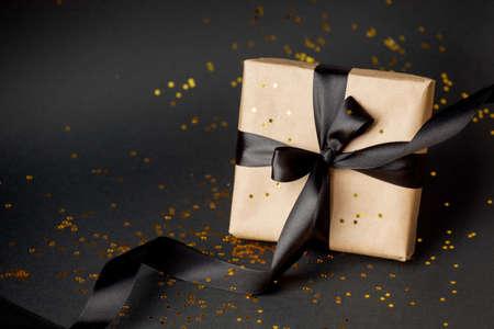 Beautiful minimal christmas, black friday golden black decor and paper craft gift box with satin black ribbon on dark black background. Flat lay design. Copy Space. Horizontal, banner, flyer Banco de Imagens