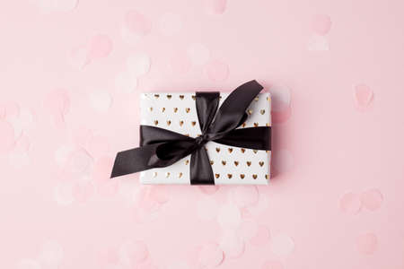 Gift or present box with black satin bow and confetti on pink pastel table top view. Flat lay composition for birthday, mother day, black friday sale, new year, christmas or wedding, copy space