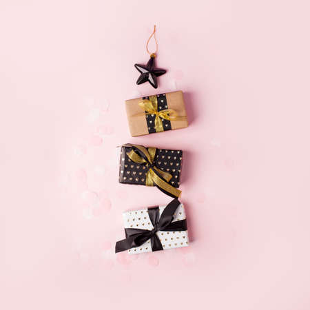 Christmas gift boxes, satin ribbon and holiday decorations laid out in the shape of a Christmas tree, overhead view on pink background, stylish luxury seasonal concept, modern idea, flyer, coupon Banco de Imagens