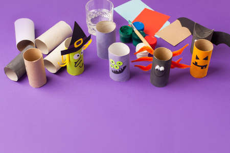 Child creates decorations for Halloween party from toilet roll. Easy eco-friendly DIY master class, craft for kids. Materials for creativity, recycle reuse concept of holiday art activities Banco de Imagens