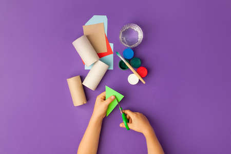Boy makes Halloween toys from paper. toilet roll tube by hands. Creative DIY for kids on traditional purple backgrpund. Home decor project party. Halloween crafts inspiration, recycle concept
