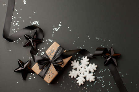 Beautiful christmas black silver decorative toys star snowflakes on dark black background. Flat lay design. Copy Space. Stylish new year concept, sale flyer, coupon, discount