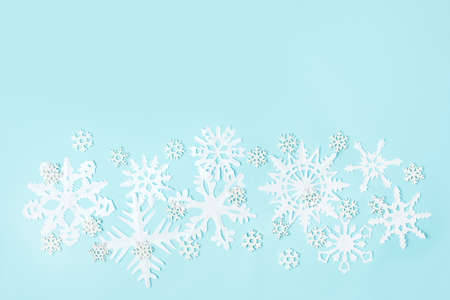 White Snowflakes cut from paper on blue background. A traditional Christmas arts and crafts easy diy project. Banner for your site, flyer, voucher, winter holiday concept