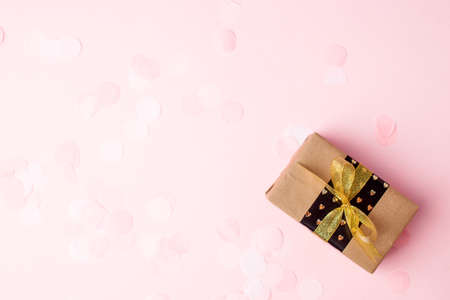Stylish gift or present box with gold bow on pink pastel background, seasonal holiday sale concept, discount, congratulations, mother day, Saint Valentine, wedding, xmas, new year