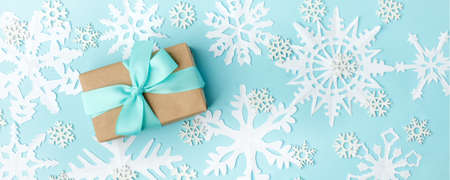 Happy New 2020 year concept, goft or present box with tissue bow and white snowflakes on blue background, copy space, xmas, christmas winter holiday creative card, banner, flyer, promotion voucher