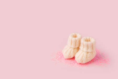 White shoes for newly born baby girl or boy on pink background, concept of expectation of baby, pregnancy, baby shower party, cute monochrome card for congratulation, banner, copy space
