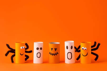 Halloween toy collection of spiders and ghosts on orange for Halloween concept background. Paper crafts, easy DIY. Handcraft creative idea from toilet tube, recycle concept, flyer, banner Banco de Imagens
