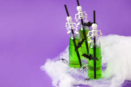 Halloweens spooky drink, green cocktail for party in glass bottle with creepy decoration - spider web, skeleton straw on traditional purple background, bright flyer, coupon, banner for holidays adds