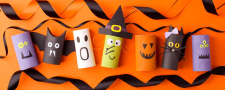 Halloween and decoration concept - monsters from toilet paper roll tube on orange. Simple easy diy creative idea. Eco-friendly reuse recycle decor, kindergarten paper craft, seasonal holiday banner Banco de Imagens