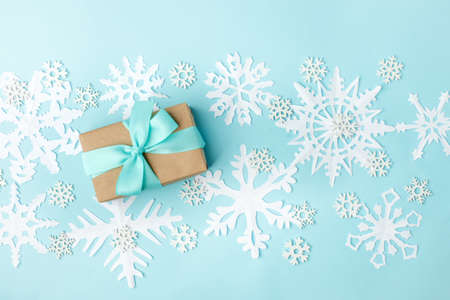 Gift or present box and white decorative wooden and papercraft snowflakes on blue background, simple minimal winter holiday background, xmas new year 2020 concept, copy space, anniversary card