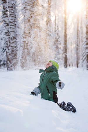 Portrait of a cute little boy in warm clothes who play with snowflakes in winter sunny frosty day, beautiful seasonal card, Siberia nature, kids play, having fun in wonderland forest Banque d'images