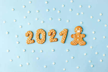 Happy New Year's set of numbers 2021, gingerbread man in face mask from ginger biscuits glazed sugar icing decoration on blue background, minimal seasonal pandemic winter holiday banner