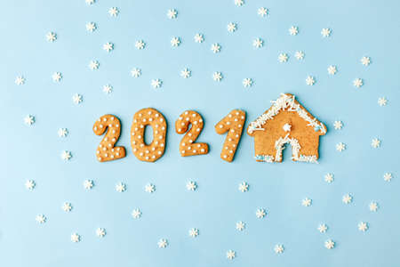 Happy New Year's set of numbers 2021 from ginger biscuits and house glazed sugar icing decoration on blue background, minimal seasonal winter holiday card, banner, flyer, coupon, stay home