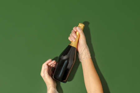 Gloved hands hold a bottle of champagne on a natural green background.