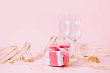 Saint Valentine days background - elegant luxury gift box and pair of champagne glasses with hearts on pink, copy space for your greering text, romance party card, seasonal holiday