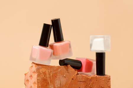 Set of nail polish in neautral colors on Minimal modern brick stone product display on beige background with podium, trendy presentation of cosmetology products, beauty industry, copy space