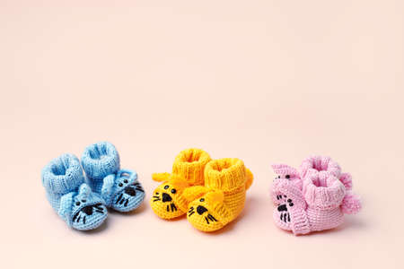 Baby shower, gender party. Boy, girl, queer, neatral. Three pairs of baby socks, booties with funny bunny decor, celebration concept when the gender of the child becomes known