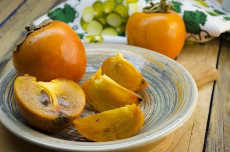 木製テーブルの上の皿に熟した柿