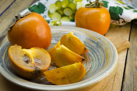 ripe persimmon on a plate on a wooden table