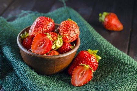 Ripe strawberry in a bowl on a close-up table