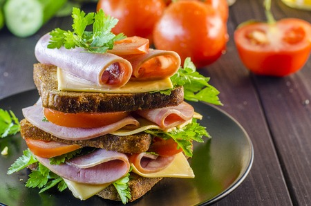 Large sandwich with sausage and cheese, cucumber and tomato