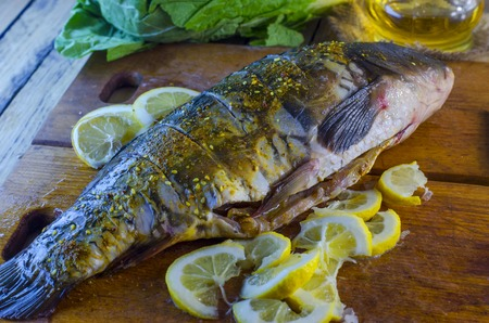 Cooking raw fish carp with lemon for baking