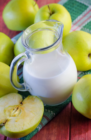 milk and ripe green apples on a wooden table 写真素材