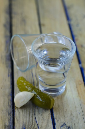 Vodka and pickled cucumber closeup on a wooden table