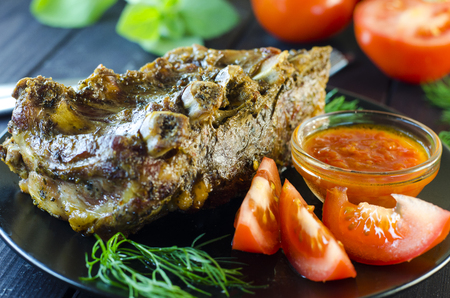 Pork meat on ribs baked in an oven with sauce and vegetables on a plate