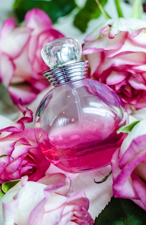 a bottle of perfume among beautiful flowers