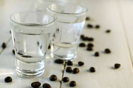 Sambuca in shot glasses and coffee beans on white background