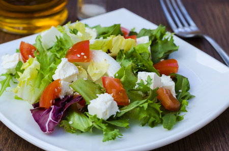 Dietary salad with tomatoes and feta cheese on a plate Фото со стока