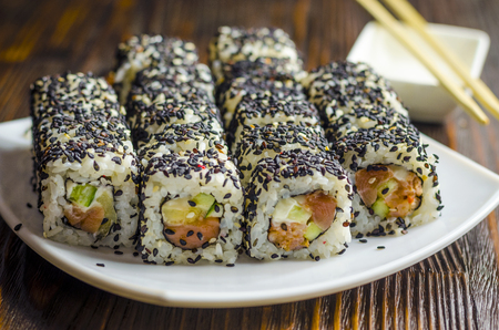 sushi with tuna in black sesame on a dark background