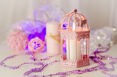 New Year and Christmas decoration with decorations and a candle lamp in pink color
