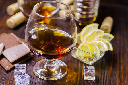 brandy in a glass with ice and lemon
