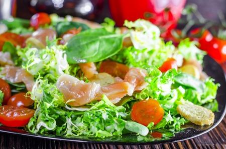Ensalada dietética con pescado rojo en un plato de cerca