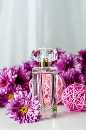 perfume with floral scent, perfume bottle and pink chrysanthemums on a white background
