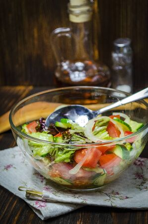 Salad from fresh vegetables in a salad bowl and seasoned with olive oil