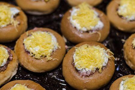 raw stuffed meat bagels on a baking sheet Stok Fotoğraf