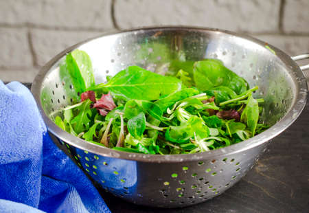 Fresh leaves of different types of salad in a colander